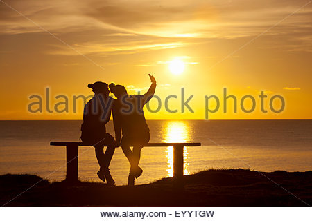 Silhouette of couple, sitting on bench taking selfie on mobile phone, against sunset over the ocean - Stock Photo