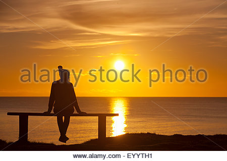 Silhouette of woman, sitting on bench, against sunset over the ocean - Stock Photo