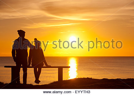 Silhouette of couple, on bench, against sunset over the ocean - Stock Photo