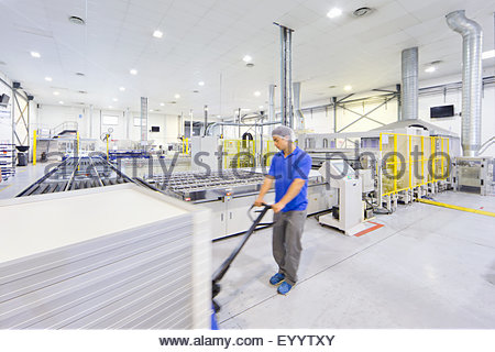 Worker pulling pallet of solar panels on factory floor - Stock Photo