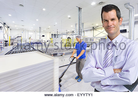 Portrait of businessman owner smiling at camera with worker pulling pallet of solar panels in factory - Stock Photo