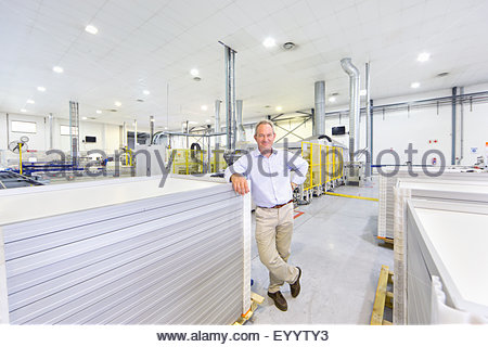 Portrait of businessman owner with solar panels on factory floor production line smiling at camera - Stock Photo