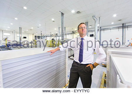 Portrait of businessman owner with solar panels on factory floor production line looking at camera - Stock Photo