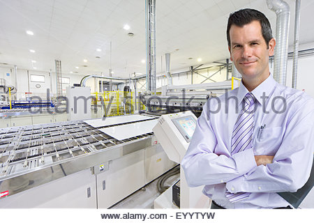 Portrait of Businessman owner smiling at camera in solar panel factory - Stock Photo