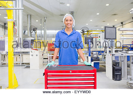 Portrait of Technician worker smiling at camera in solar panel factory - Stock Photo