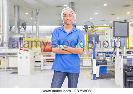 Portrait of Technician worker looking at camera in solar panel factory production line - Stock Photo