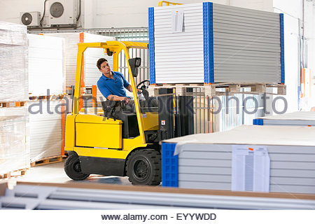 Forklift truck driver stacking solar panels in factory warehouse - Stock Photo