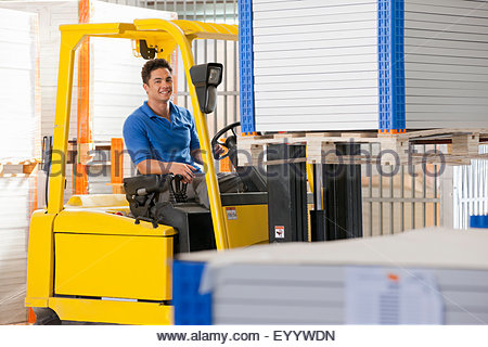 Forklift truck driver smiling at camera stacking solar panels in factory warehouse - Stock Photo