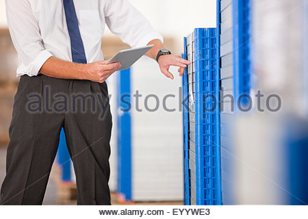 Businessman checking solar panels with digital tablet in factory warehouse - Stock Photo