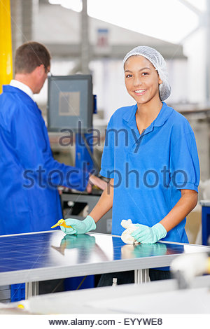 Technician worker smiling at camera cleaning and checking newly manufactured solar panels on production line - Stock Photo