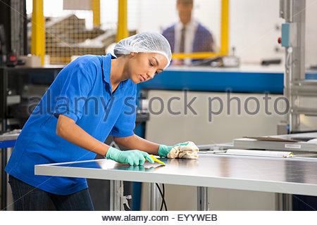 Technician worker cleaning and checking newly manufactured solar panels on production line - Stock Photo