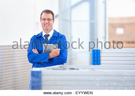 Supervisor worker smiling at camera stock checking solar panels in factory warehouse - Stock Photo