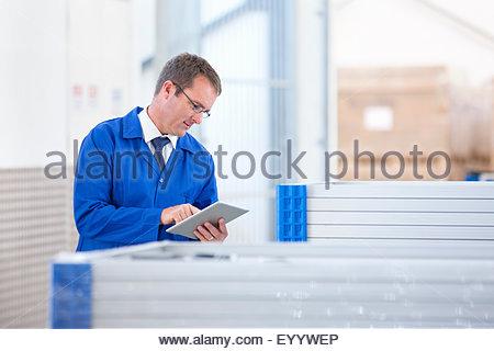 Supervisor worker stock checking solar panels in factory warehouse - Stock Photo