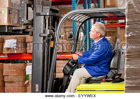 Worker driving forklift stacking boxes in warehouse - Stock Photo