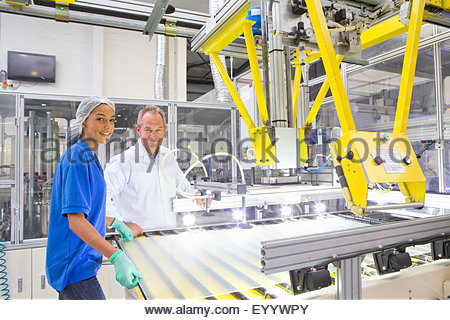 Engineer and Technician worker smiling at camera coating glass for use in production of solar panels - Stock Photo