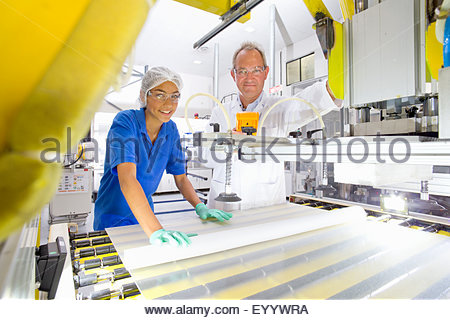 Engineer smiling at camera checking worker coating solar panel glass on production line on factory floor - Stock Photo