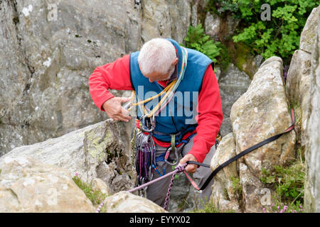 Experienced rock climber wearing a climbing harness preparing a belay tying in with a top rope tape and karabiners. - Stock Photo