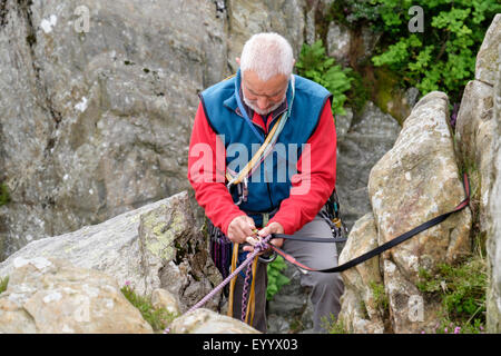 Experienced rock climber preparing to climb setting up a belay tying in with a top rope tape and karabiners. North - Stock Photo