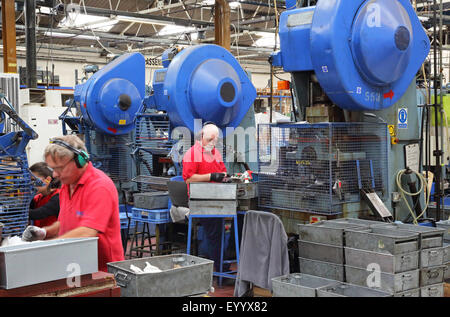 Workers in a factory manufacturing metal components for the construction industry using large steel pressing machines - Stock Photo