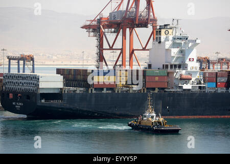 Tug pulling containership MSC Valencia away from berth. Port of Salalah Oman. - Stock Photo