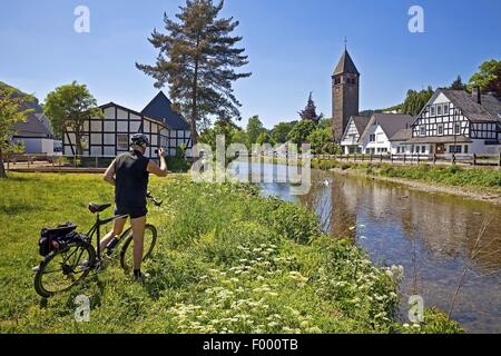 cyclist takes a photo of the River Lenne district Saalhausen, Germany, North Rhine-Westphalia, Sauerland, Lennestadt - Stock Photo