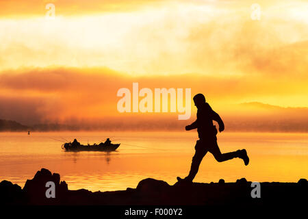 Sunrise over men fishing in a boat on Lake Windermere in Ambleside, Lake District, UK and a man running past. - Stock Photo