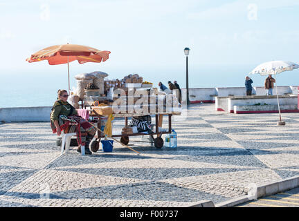 A woman sells nuts and dried fruit on the square in old town Nazare (Sítio), Portugal - Stock Photo