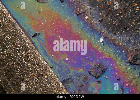 film of oil on a street at the roadside, Germany - Stock Photo