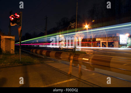 train crossing an railway crossing at night, Germany - Stock Photo
