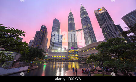 Water Fountain at Suria KLCC with Petronas Towers and Office Buildings at Blue Hour sunset at Night. - Stock Photo
