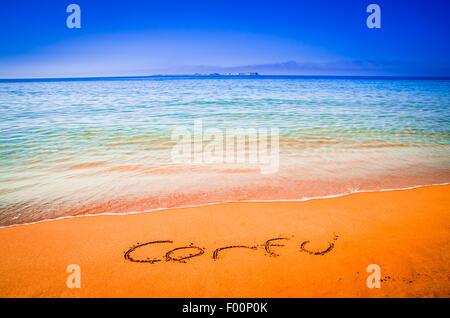 Corfu word written on a sandy golden beach, Greece. Selective focus. - Stock Photo