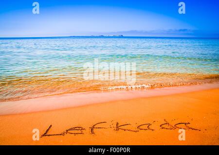 Lefkada word written on a sandy golden beach, Greece. Selective focus. - Stock Photo