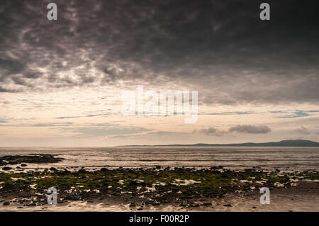 An early evening photograph with dark clouds looking across Loch Indaal from Big strand to the Rinns of Islay - Stock Photo