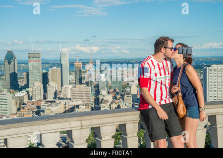 Young couple using a selfie stick in front of Montreal Skyline, Kondiaronk belvedere. - Stock Photo