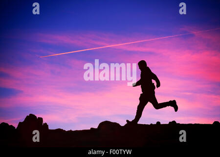 plane contrail at sunset near Windermere UK, with a man running past. - Stock Photo