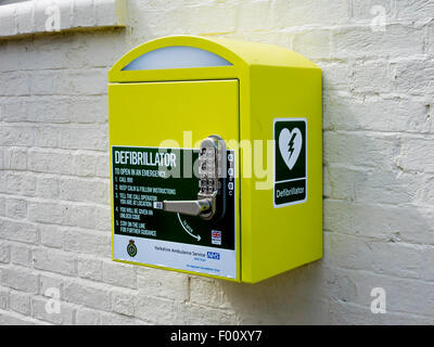 Heart defibrillator life saving equipment for cardiac arrest with code lock for public use in a village in  England - Stock Photo