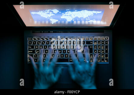 Hands are typing on a laptop computer in the dark with illuminated keyboard and a world map on the screen - Stock Photo