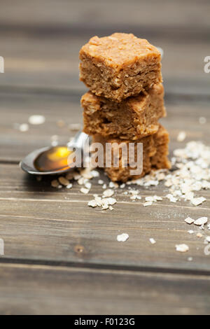 Stack of chewy and indulgent flapjacks on a wooden background surrounded by ingredients - Stock Photo