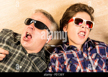 Father and son listening to music together with headphones stretched on a wooden floor at home - Stock Photo