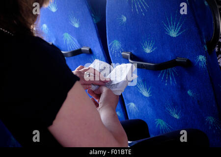 A religious Jewish woman reading the book of Psalms in Hebrew in a bus in Israel - Stock Photo