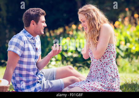 Handsome man doing marriage proposal to his girlfriend - Stock Photo