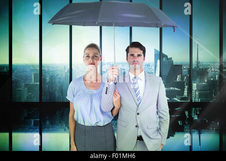 Composite image of business people holding a black umbrella - Stock Photo