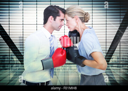 Composite image of business people wearing and boxing red gloves - Stock Photo