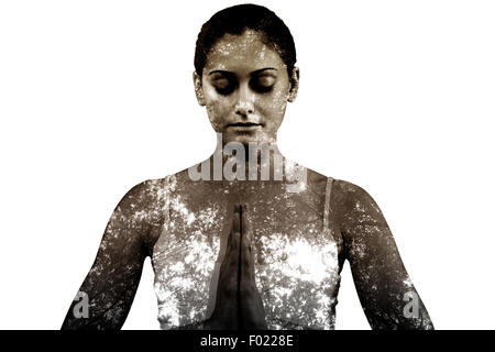 Composite image of peaceful woman in white sitting in lotus pose - Stock Photo