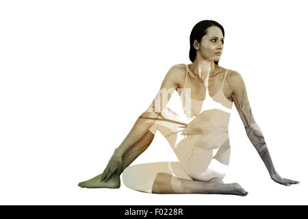 Composite image of fit woman doing the half spinal twist pose in fitness studio - Stock Photo