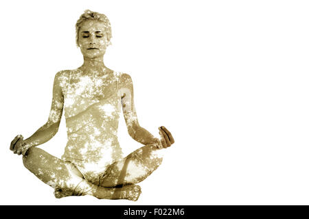 Composite image of toned young woman sitting in lotus pose with eyes closed - Stock Photo