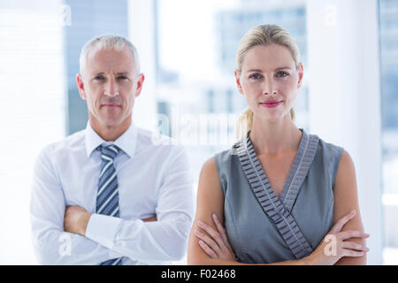Two business people looking at the camera - Stock Photo