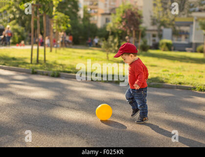 Baby boy playing football in the street - Stock Photo