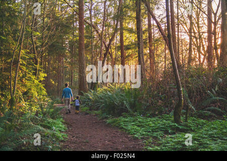 Father and son walking in the woods - Stock Photo