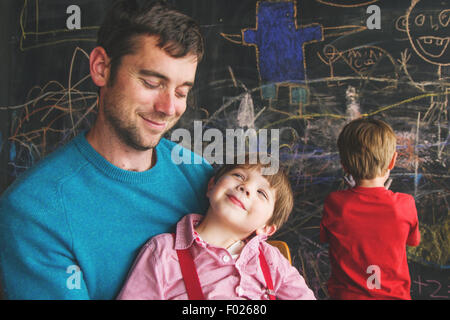 Young boy sitting on father's lap with boy in background - Stock Photo